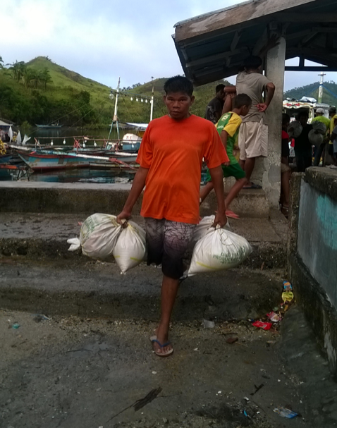 A man carries the ActionAid foodpacks in Barangay Cagutsan for relief distribution.
